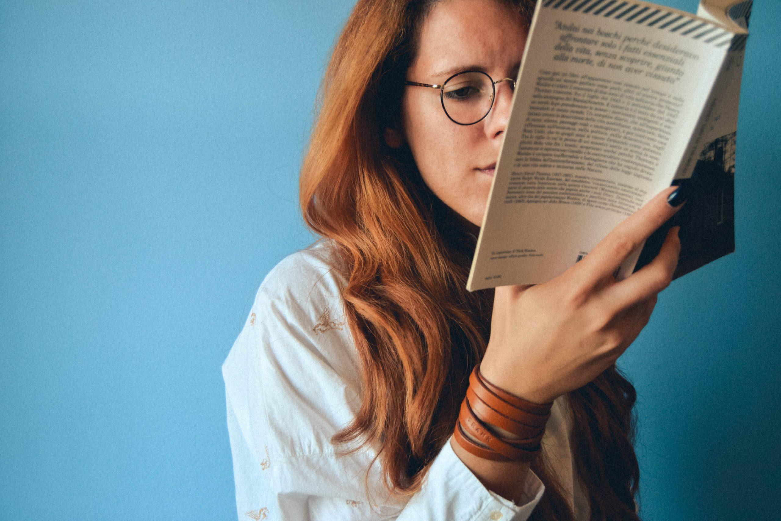Mujer leyendo un libro sobre pared azul